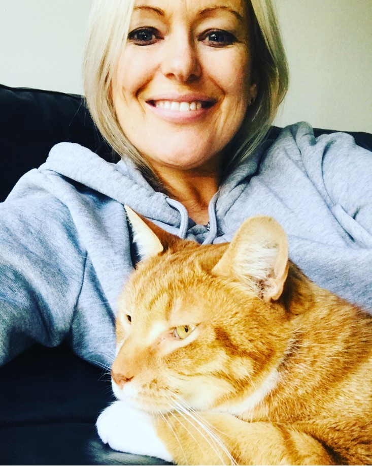 woman looking at the camera and a cat on her lap